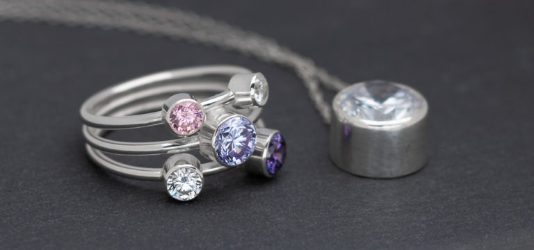Silver ring with a number of round faceted stones and a silver setting also with a faceted stone on a slate background