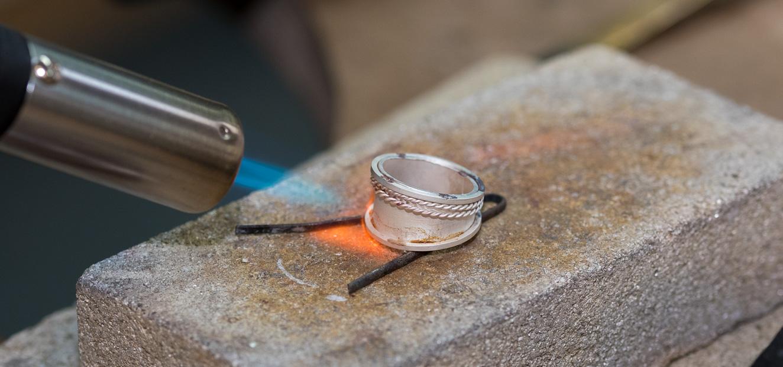 Tutor demonstrating soldering a byzantine ring