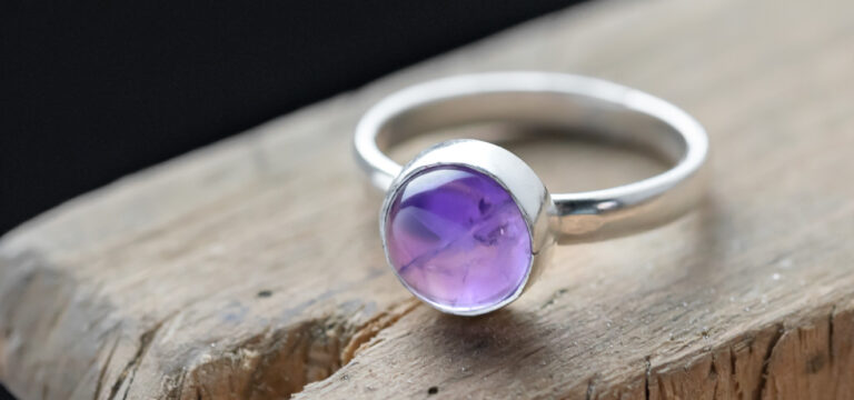 silver ring with cabochon stone setting with a amethyst stone on a jewellery bench peg